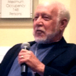 A photo of Robert Becker speaking into a microphone during a 2013 event.